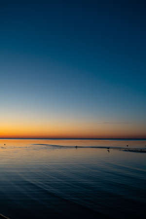 Vivid amazing sunset in Baltic States - Dusk in the sea with horizon illuminates by the sun