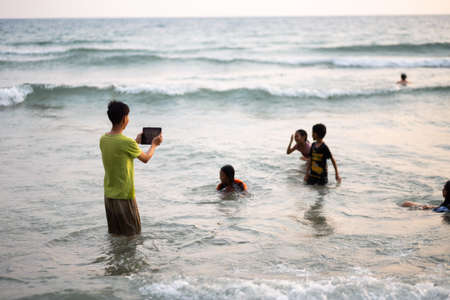 KO CHANG, THAILAND - APRIL 10, 2018: Thay asian children playing in sea - Boy takes photo via a tablet Редакционное