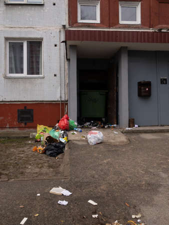 RIGA, LATVIA - MARCH 21, 2019: Trash everywhere outside of a house - Decayed bin