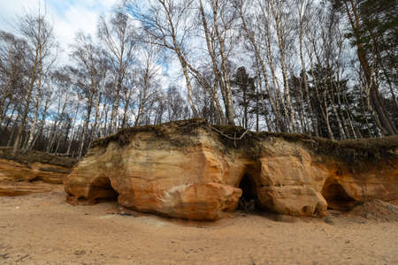 Limestone beach at the Baltic Sea with beautiful sand pattern and vivid red and orange color - Tourist writings on the walls and rocks and sand - Veczemju Klintis, Latvia - April 13, 2019