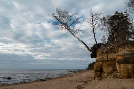 Kalksteinstrand an der Ostsee mit schönem Sandmuster und lebendiger roter und oranger Farbe - Touristische Schriften an den Wänden und Felsen und Sand - Veczemju Klintis, Lettland - 13. April 2019 Standard-Bild