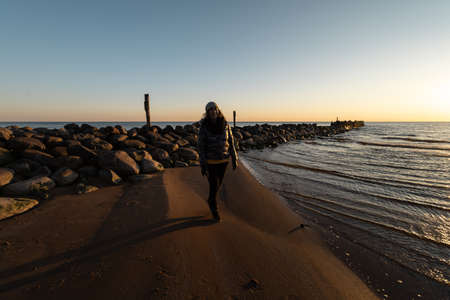 Woman enjoying a cold Spring sunset at a boulder beach near the Baltic Sea