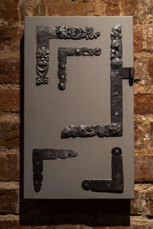 Old door holes and handles - Wooden entrance on brick walls - Handles made of metal