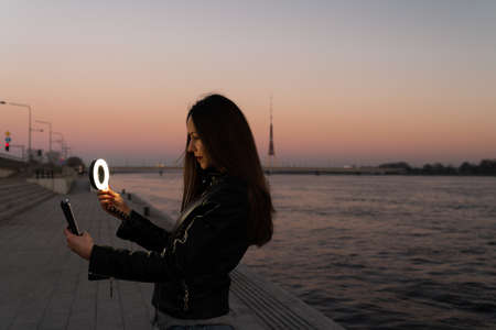 Young woman taking a selfie using a ring flash as a fill light at a sunset with a view over river Daugava 版權商用圖片 - 121853364