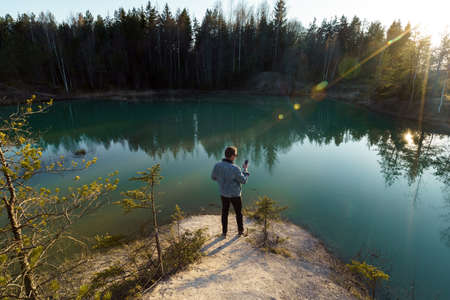 Young man take travel photos - Beautiful turquoise lake in Latvia - Meditirenian style colors in Baltic states - Lackroga ezers Stockfoto