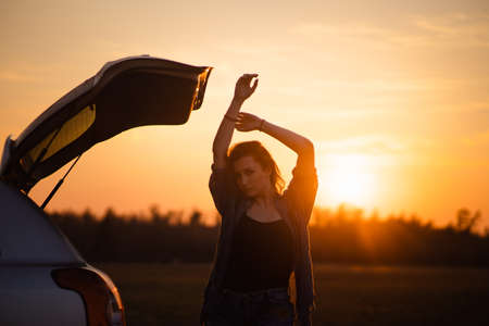 Beautiful young woman happy and dancing in a cars trunk during a road trip in Europe in the last minutes of Golden Hour sunset