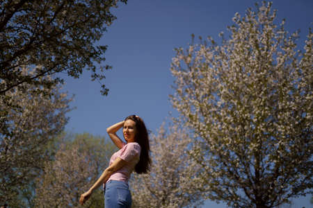 Successful business woman enjoys her leisure free time in a park with blossoming sakura cherry trees wearing jeans, pink t-shirt and long hair from behind back Stockfoto