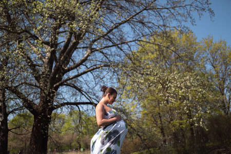 Young traveler pregnant woman walking, running, turning around and enjoys her leisure free time in a park with blossoming sakura cherry trees wearing a summer light long dress with flower pattern Archivio Fotografico - 121852563