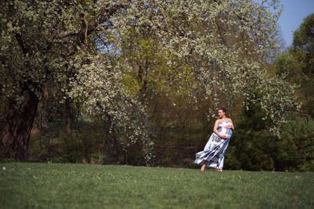 Young traveler pregnant woman walking, running, turning around and enjoys her leisure free time in a park with blossoming sakura cherry trees wearing a summer light long dress with flower pattern 스톡 콘텐츠