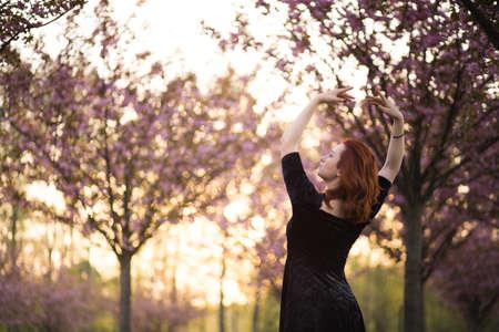 Fröhliche junge Reisetänzerin, die Freizeit in einem Sakura-Kirschblütenpark genießt - Kaukasisches weißes Rothaariges Mädchen - Gekleideter schwarzer Halsreif, schwarzes Kleid und schwarze Golfs