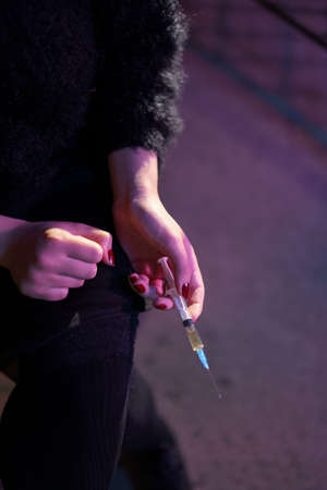 Syringe close up in hands of a drug addiction redhead caucasian white young woman wearing black sweater, skirt and chocker - Anxiety, depression and danger feeling