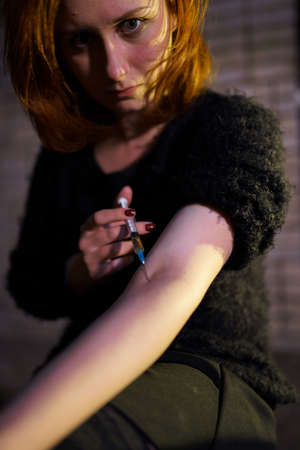Veins syringe close up in hands of a drug addiction redhead caucasian white young woman wearing black sweater, skirt and chocker - Anxiety, depression and danger feeling