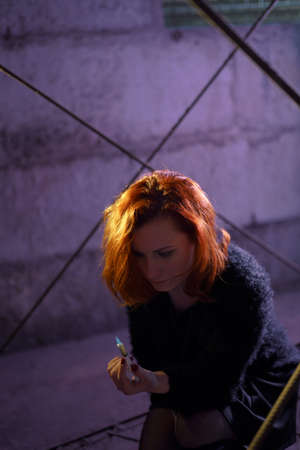 Face portrait close up of drug addiction redhead caucasian white young woman wearing black sweater, skirt and chocker with syringe and pills in the background - Anxiety, depression and danger feeling Stock Photo