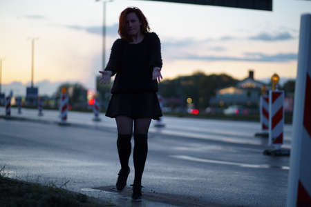 Active traveler dancer woman performing on a road construction site at sunset time with car lights passing by wearing black skirt and warm sweater and a chocker