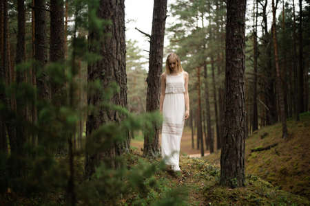 Walking Beautiful young blonde woman forest nymph in white dress in evergreen wood