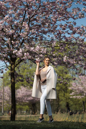 Beautiful blonde young woman in Sakura Cherry Blossom park in Spring enjoying nature and free time during her traveling tourist free time - Wearing white pants and t-shirt with a beige jacket