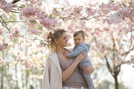 Young mother mom holding her little baby son boy child under blossoming SAKURA Cherry trees with falling pink petals and beautiful flowers