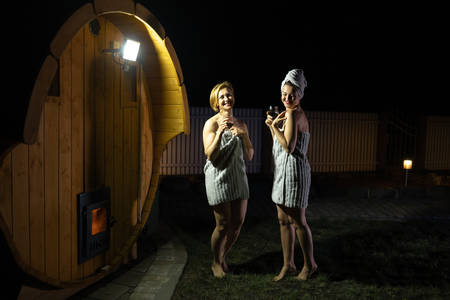 Two girlfriends women drinking red wine from glasses outsite near a wooden mobile sauna wearing just towels