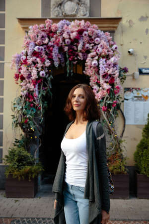 Happy woman portrait sexy moving on the flower arch background in beautiful Riga old town