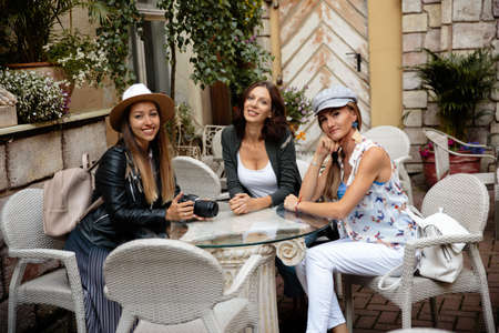 Three traveling girl friends sitting in italian restaurant with light backpacks exploring Riga city - Travel tourism concept after transfer from airport - Wearing hats and jeans