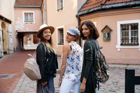Three traveling girl friends with light backpacks walking exploring Riga city - Travel tourism concept after transfer from airport - Wearing hats and jeans 版權商用圖片