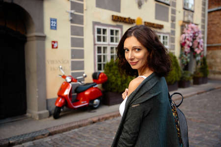 Happy woman portrait sexy moving on red motorcycle bike background in beautiful Riga old town 版權商用圖片