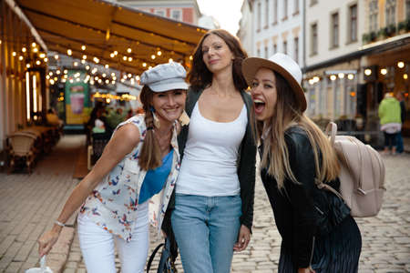 Chatting and laughing Three traveling girl friends with light backpacks exploring Riga city - Travel tourism concept after transfer from airport - Wearing hats and jeans 版權商用圖片