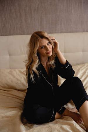 Sexy tedere blonde vrouw in avondjurk gewaad en zwarte lingerie voorbereiden om te gaan slapen naar bed - mooi krullend haar