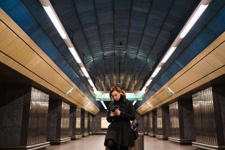 Redhead woman using phone texting in a Prague metro subway