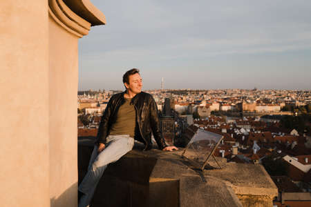 Happy man start fresh new life looking at Prague centre and Charles Bridge view from above and using phone to take a selfie photo