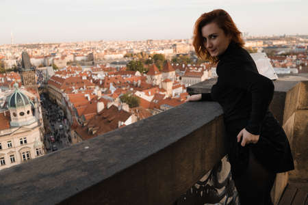 Happy readhead woman start fresh new life looking at Prague centre and Charles Bridge view from above