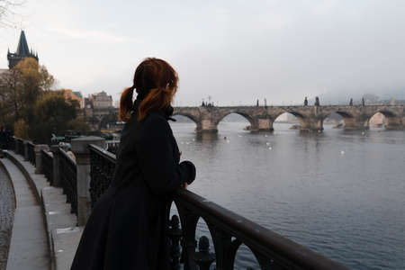 Redhead woman from her back and Charles Bridge view in early morning in Prague, Czech Republic - Fog and mist