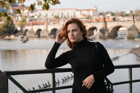 Happy redhead tourist traveler in Prague, Czech Republic wearing black sweater with Charles Bridge in the background 版權商用圖片