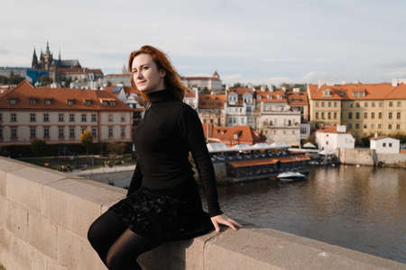 Happy redhead tourist traveler in Prague, Czech Republic wearing black sweater sitting at Charles Bridge 版權商用圖片
