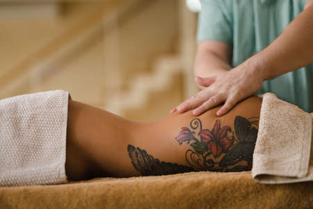 Blonde woman relaxing receiving back massage from male physiotherapist in beauty salon lying on massage table. Young girl with tattoos relaxing in spa center concept - Medium Stockfoto