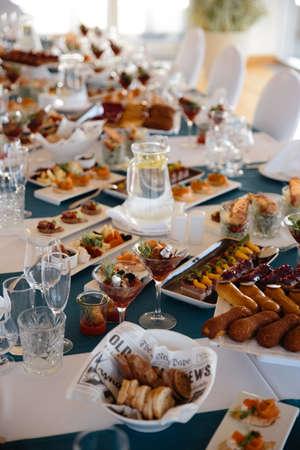 Cibo servito sul tavolo in una sala bianca durante una festa di compleanno nell'Europa orientale Baltico Riga Lettonia - Colori blu e verde acqua - Canape, snack e bevande leggere Archivio Fotografico