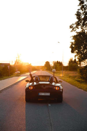 Wedding Just Married sign black rodster cabrio coupe car with bride and groom leaving into sunset in Eastern European Baltic Riga Latvia 스톡 콘텐츠