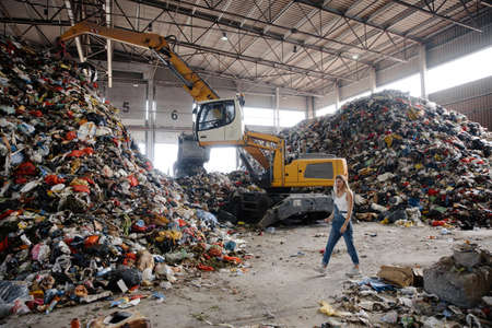 Nature pollution activist at a huge trash dump - Young blonde woman - Looking at all the human waste and plastic in our world - Tractor operating in the background in Eastern Europe Latvia Riga Reklamní fotografie
