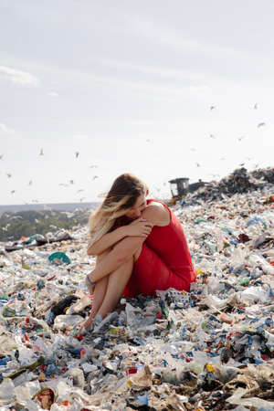 Nature pollution activist at a huge trash dump outdoors - Young blonde woman in a red dress - Looking at all the human waste and plastic in our world - Seagulls flying in Eastern Europe Latvia Riga Reklamní fotografie