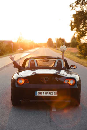 Wedding Just Married sign black rodster cabrio coupe car with bride and groom leaving into sunset in Eastern European Baltic Riga Latvia 免版税图像