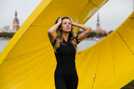 Fit slim woman warming up and exercising near Riga river Daugava at sunset - Shot of urban city wellness concept - Eastern European Latvia Riga