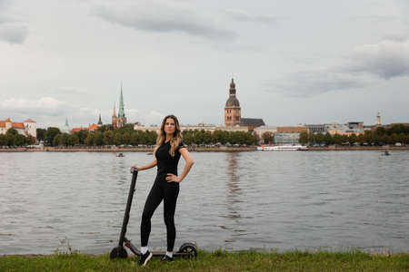 Fit Woman by electric scooter with a river city background - Shot of Modern transportation gadget and popular futuristic device among young people - Eastern European Latvia Riga