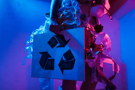 RECYCLE SIGN: Portrait of smiling female eco fighter wearing trash dress made of plastic and cardboard helping spread environment cleaning nature from pollution awareness concept - Vivid crazy neon saturated colors Violet Purple Blue