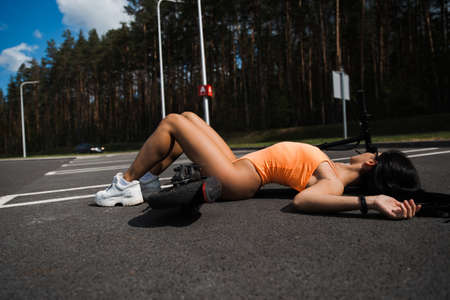 Sexy hot woman laying at electric scooter Traffic accident crash concept at parking lot wearing body swimwear lingerie and sunglasses - Emission free eco friendly transportation