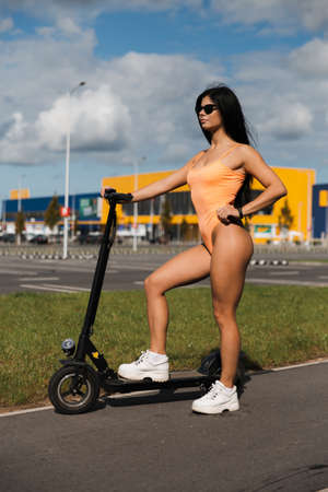 Sexy hot woman riding electric scooter at parking lot wearing body swimwear lingerie and sunglasses - Emission free eco friendly transportation