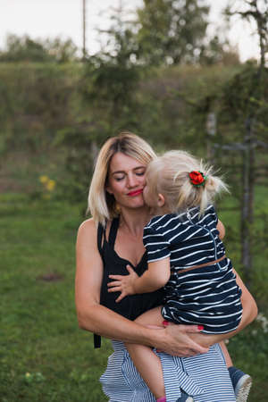 Mother gets kissed by blonde daugher in striped dress in park. Stock fotó