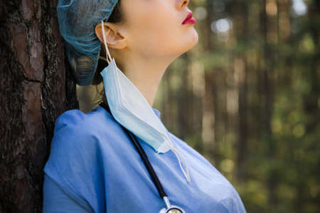 Tired but happy female doctor took off surgical mask in forest. Wear surgical mask and gown Stock fotó