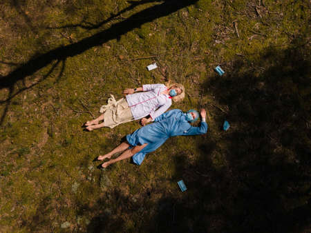 Two medics in surgical masks lying in forest and chatting