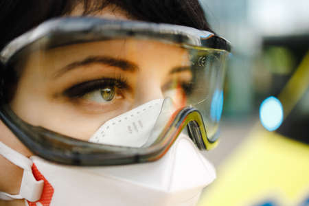 Macro eye view of sad female paramedic wearing protective goggles and medical respirator feeling alert with blue lights blinking in background