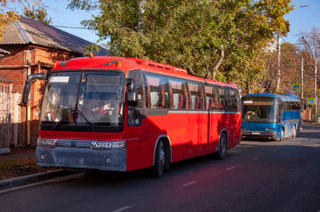 Two red and blue passenger buses standing along the road parked Stockfoto